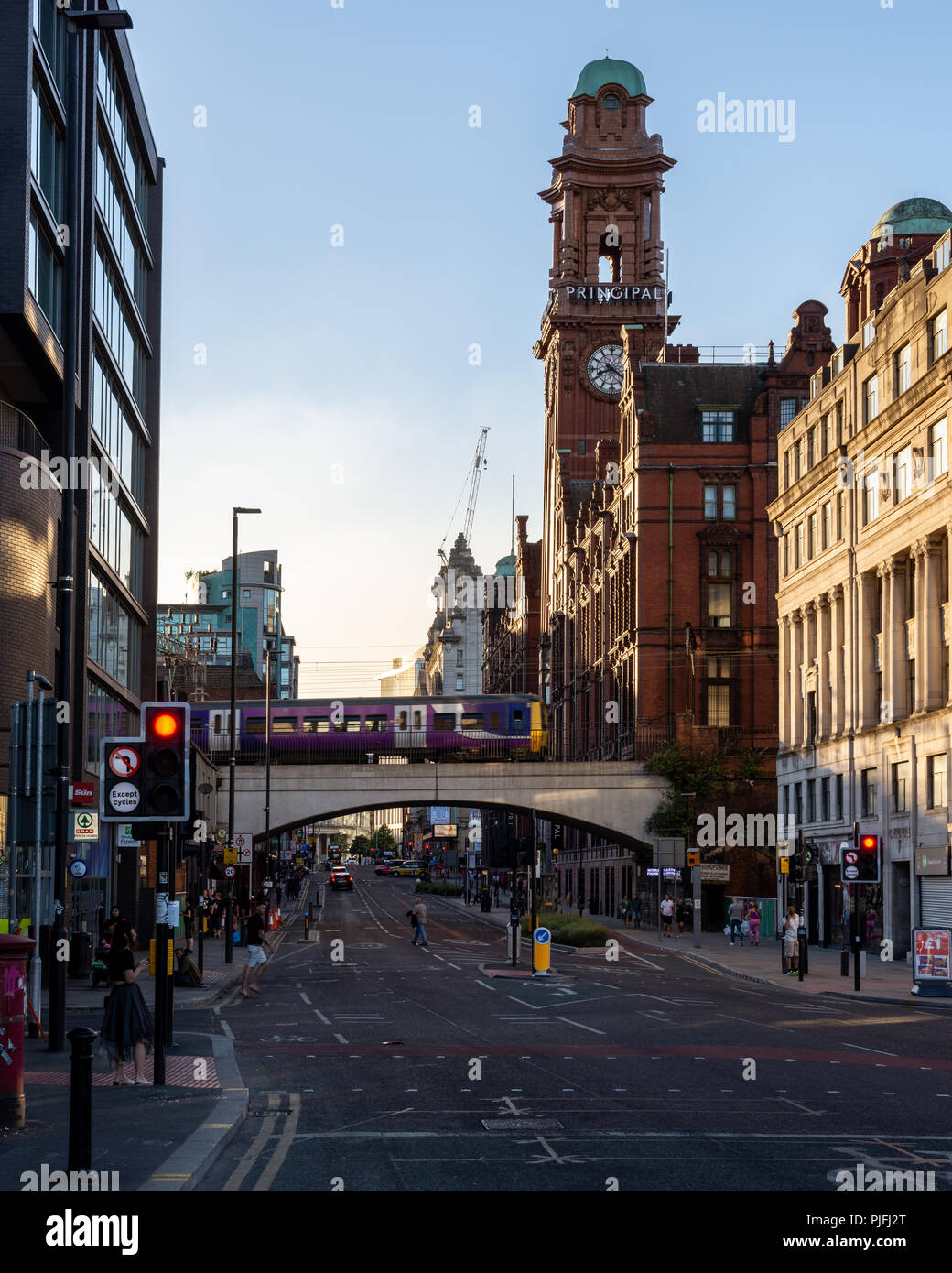 Manchester, England, UK - June 30, 2018: A Northern Rail Class 323 electric commuter train crosses Manchester's Oxford Road, with the clock tower of t - Stock Image