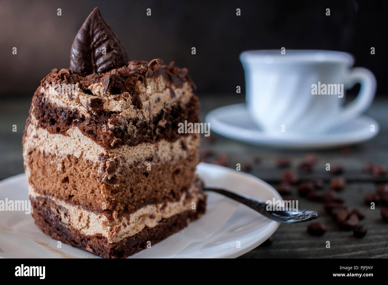 Tasty piece of chocolate cake on wooden table background - Stock Image
