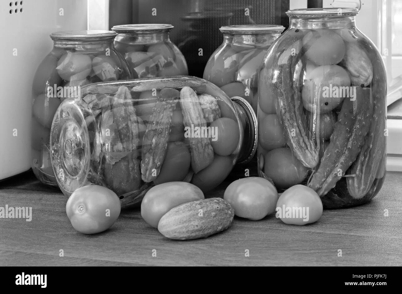 Home preservation: large glass jars with red ripe tomatoes and pickled cucumbers, sealed metallid. Black-and-white image. - Stock Image