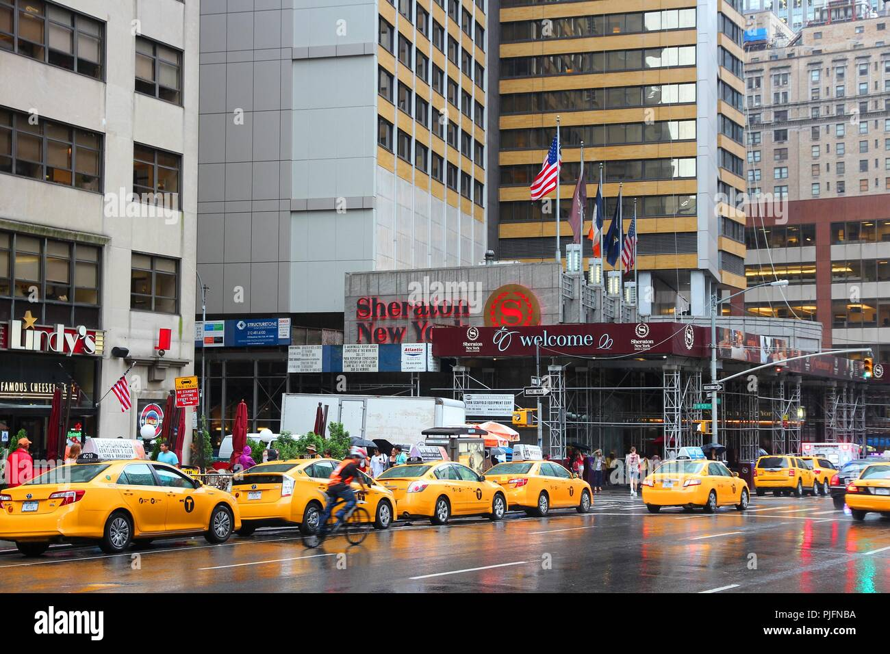 NEW YORK, USA - JULY 1, 2013: People walk along taxi filled 7th Avenue in New York.  As of 2012 there were 13,237 yellow taxi cabs registered in New Y Stock Photo