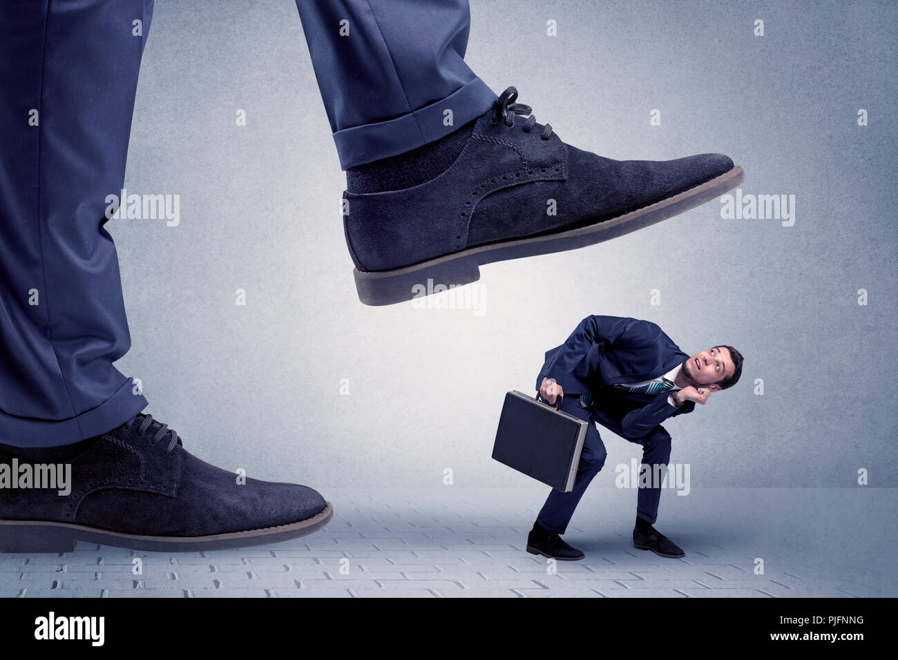 Young handsome businessman getting crushed by a big formal shoe  - Stock Image