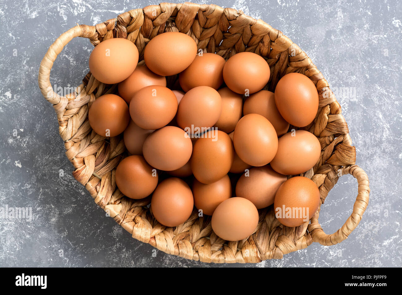 Close-up of a brown chicken egg in a basket on a gray background. Top view,flat lay Stock Photo