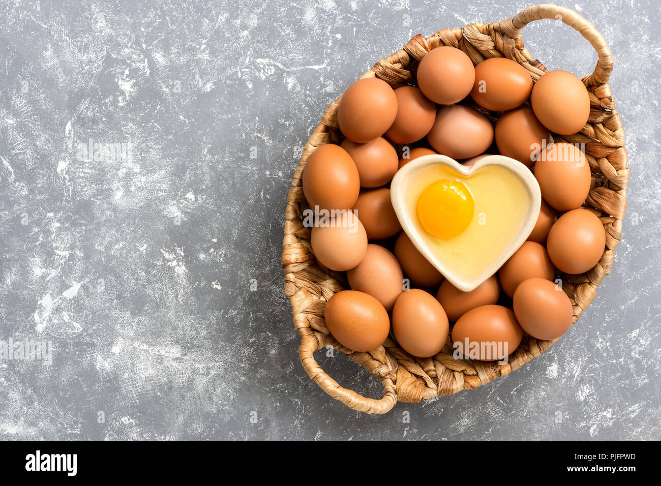 A raw egg in a bowl in the shape of a heart, a basket with brown eggs on a gray background. Top view, copy space, flat lay. Stock Photo