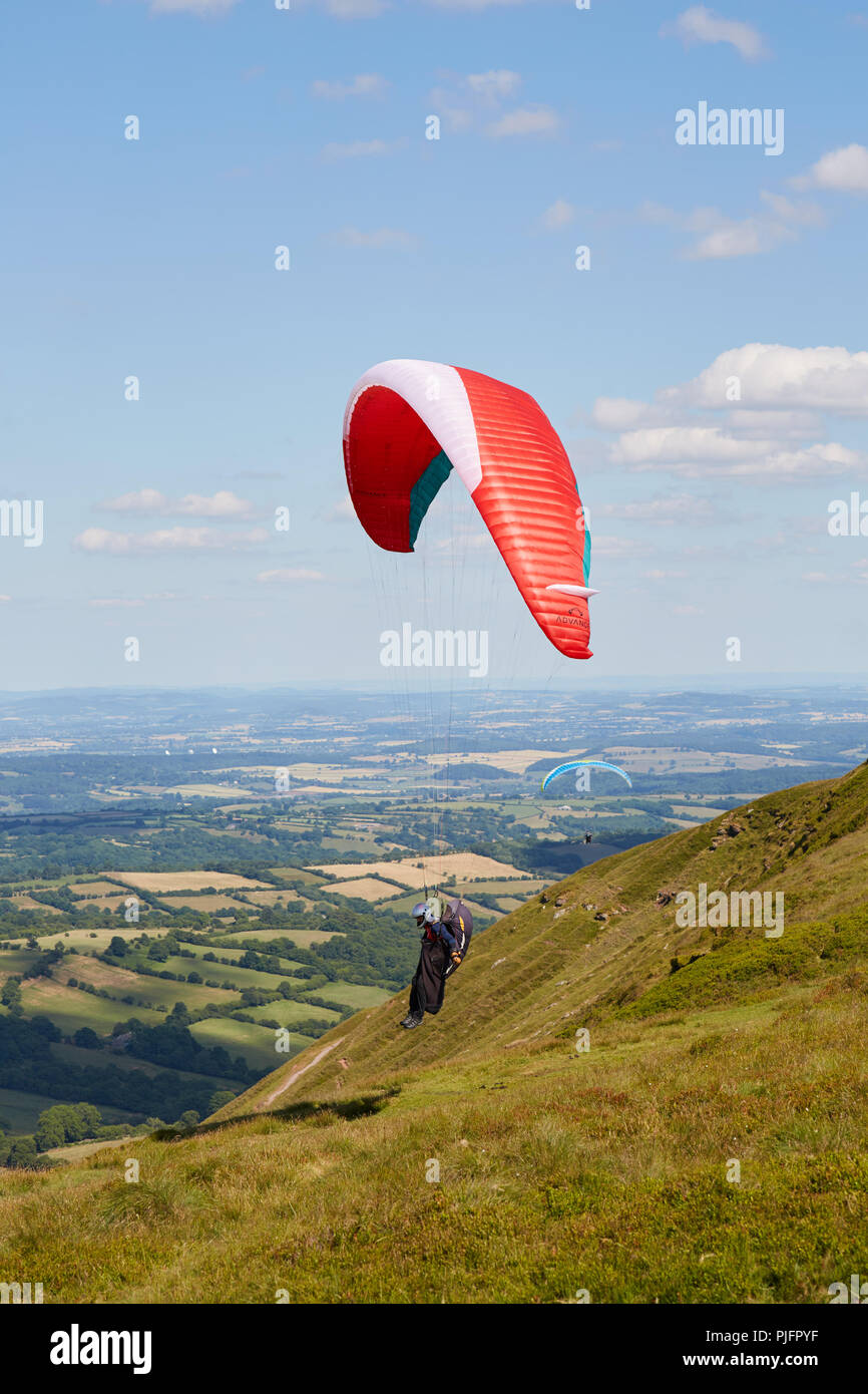 A lone paraglider lands on Hay Bluff above green fields in Wales UK on a sunny day - Stock Image