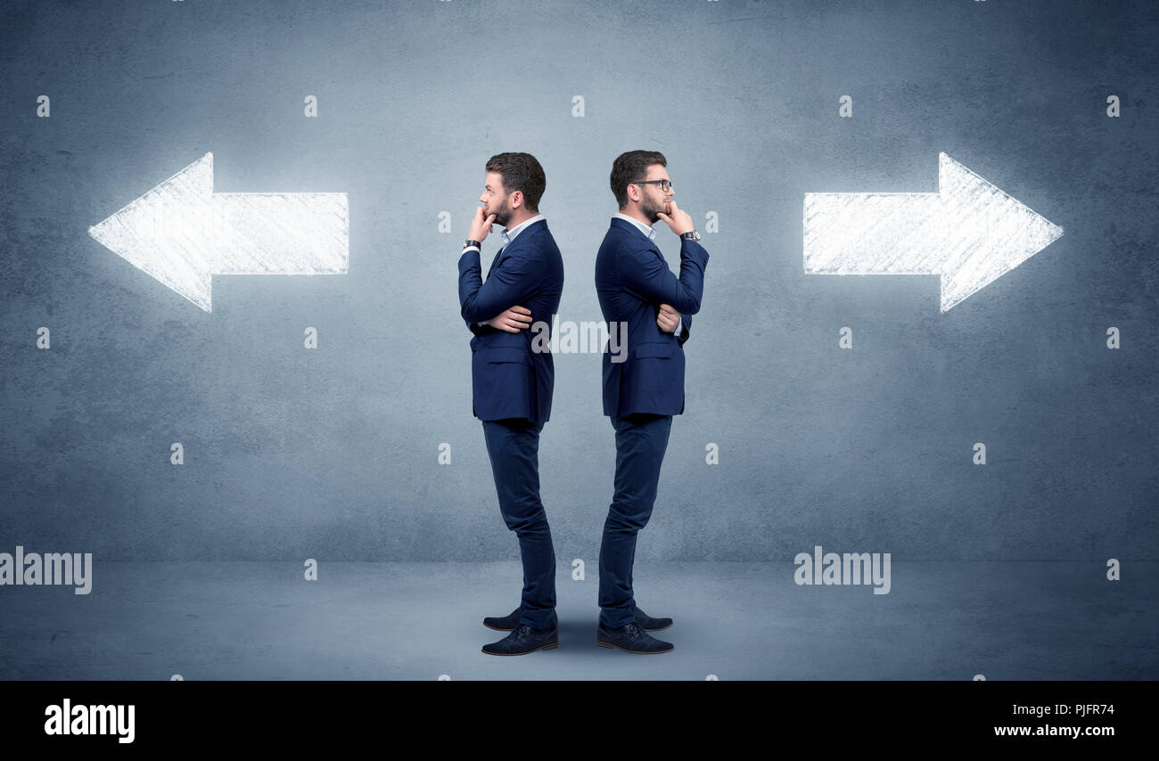 Young conflicted businessman choosing between two directions  - Stock Image