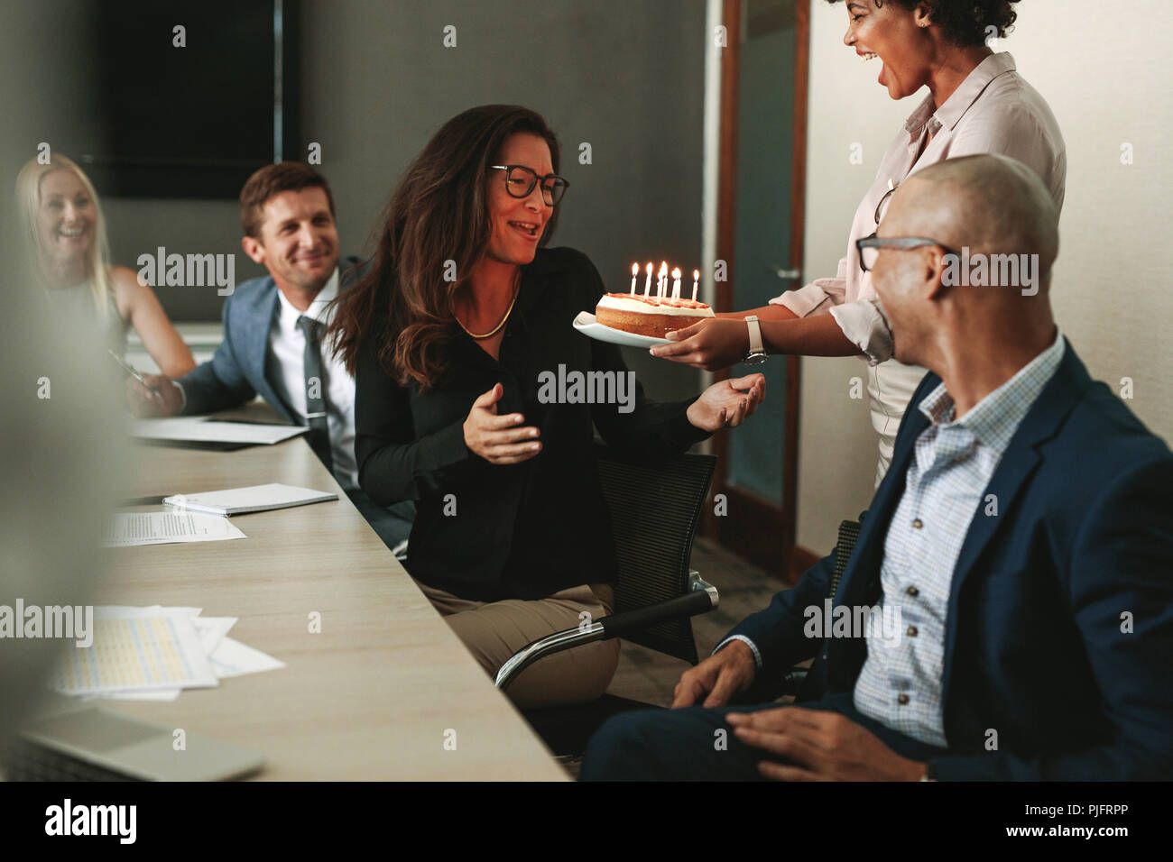African woman giving a birthday cake to female executive in conference room. Workers celebrating colleague's birthday in office during a meeting. - Stock Image