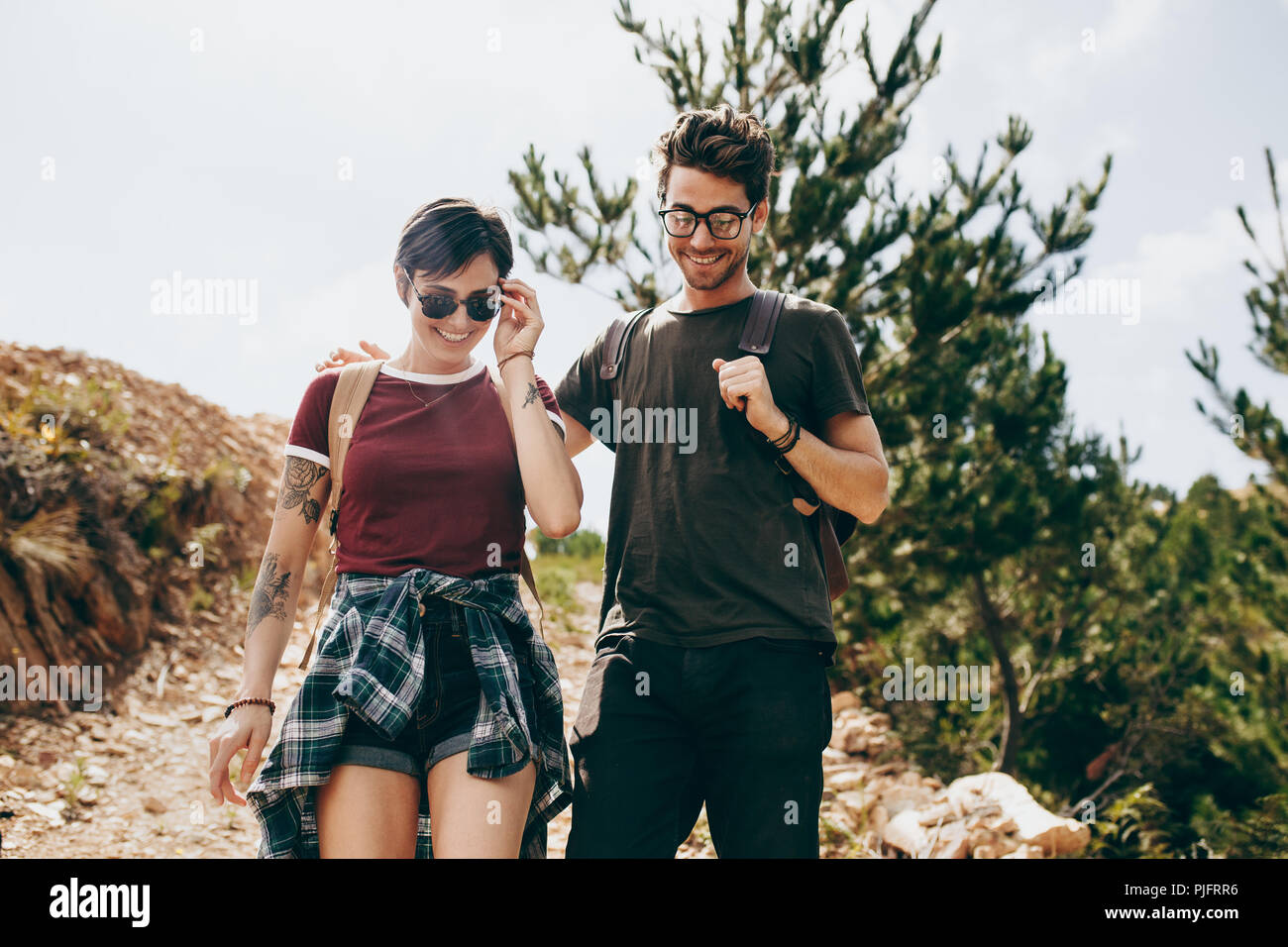 Couple hiking in a countryside location. Man and woman trekking through a forest wearing backpacks. - Stock Image