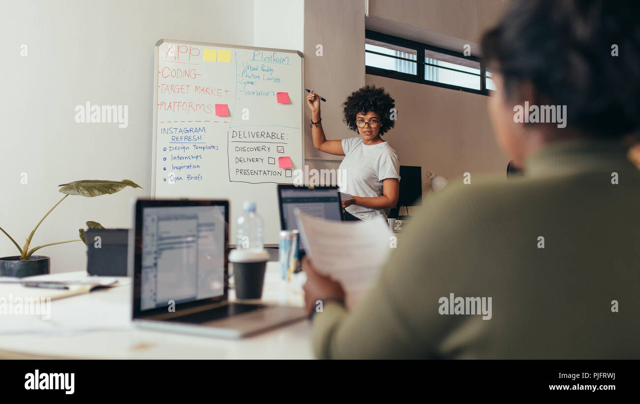 African businesswoman giving presentation to colleagues at tech startup. Presentation at startup office for new app development. - Stock Image