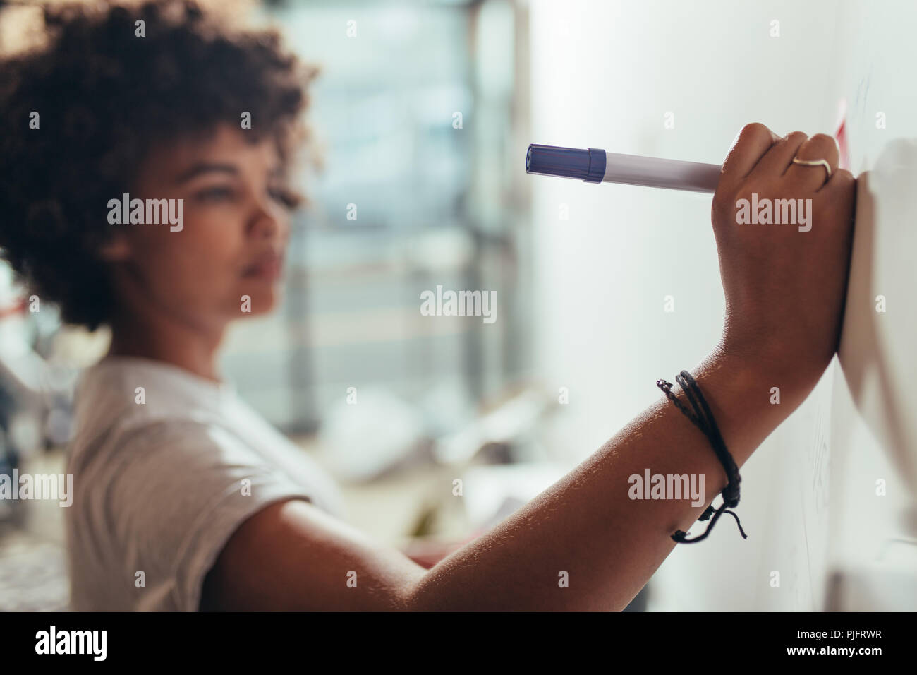 Close up of woman writing on white board during a business project meeting. Focus on female hands writing with a marker pen on presentation board. - Stock Image