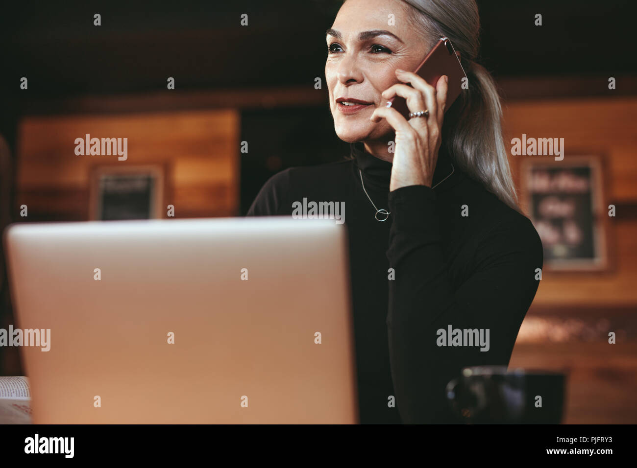 Portrait of beautiful senior woman sitting at coffee shop and talking on cell phone. Businesswoman making phone call while sitting at cafe. - Stock Image