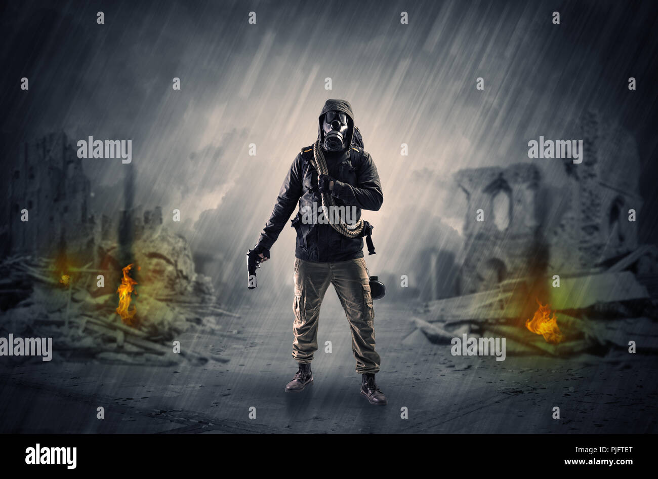 Destroyed place after a catastrophe with man in gas mask and weapon on his hand  - Stock Image