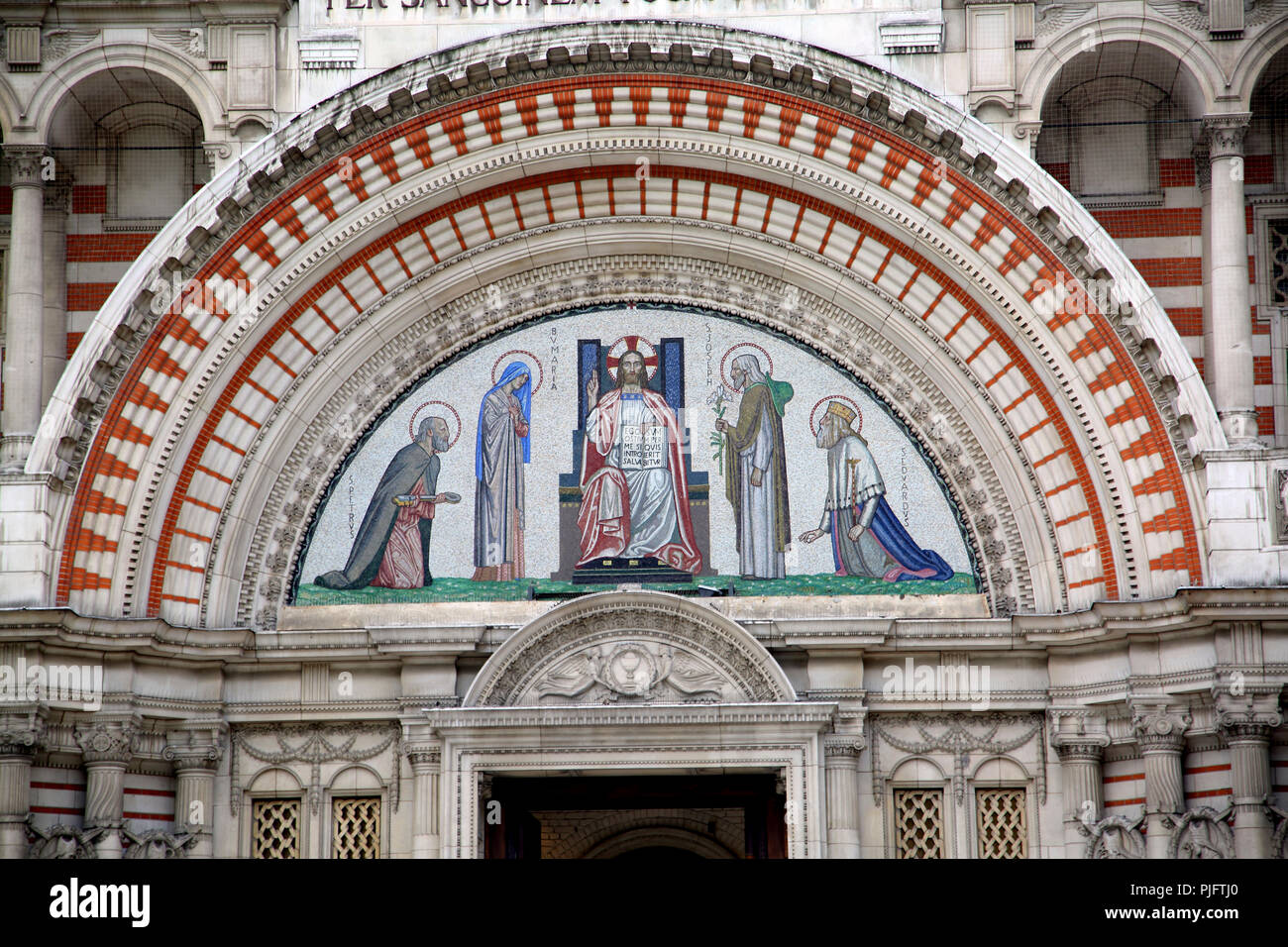 Victoria London England Westminster Cathedral North West Portal Arch Tympanum shows Mosaic depicting Saint Peter, Virgin Mary, Jesus Christ as Pantocr - Stock Image