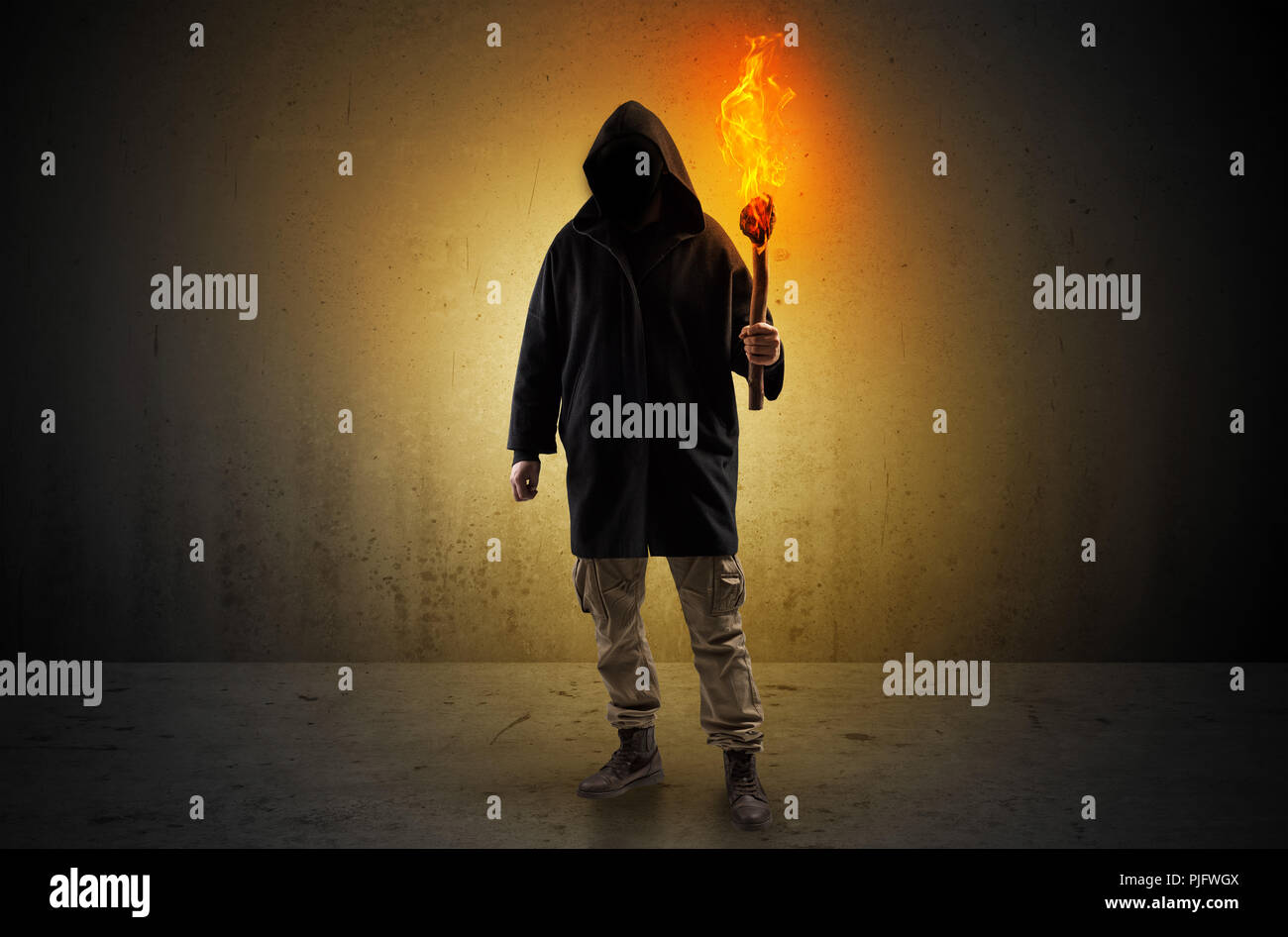 Ugly scary man with burning flambeau walking in an empty space - Stock Image
