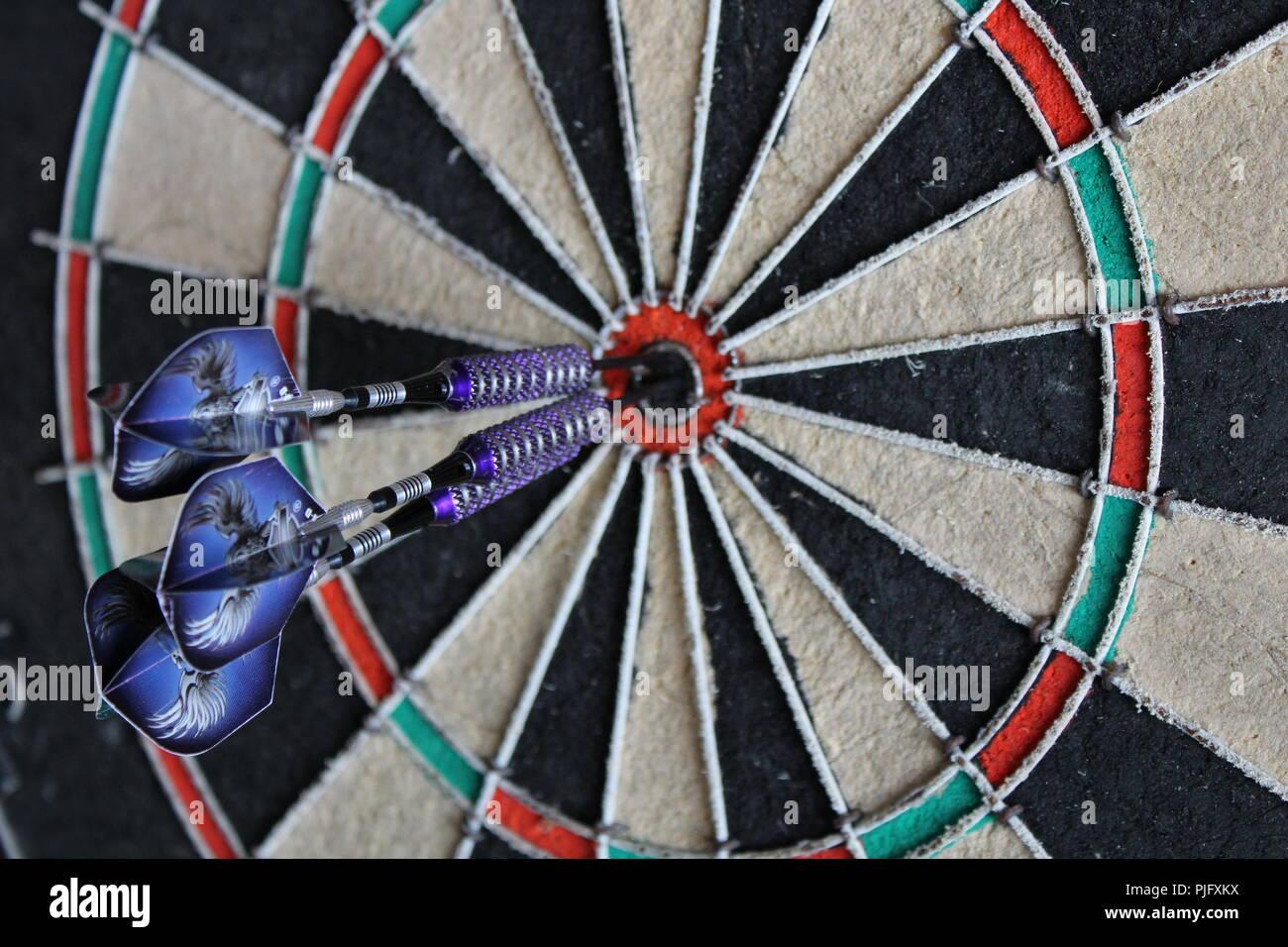dart board with three darts in the bullseye closeup - Stock Image