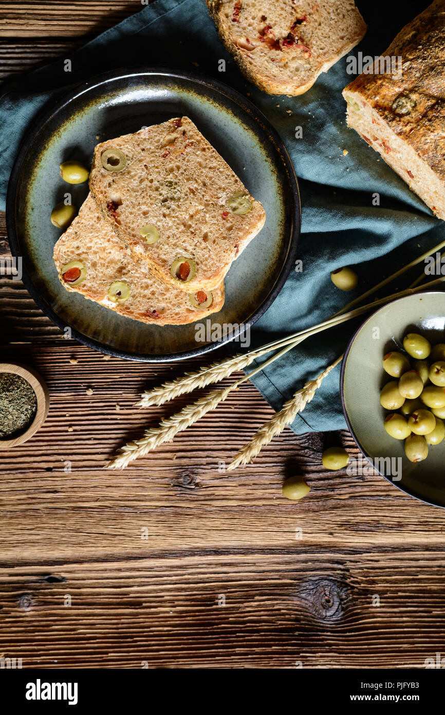 Homemade loaf of bread with sun dried tomato and green olives - Stock Image