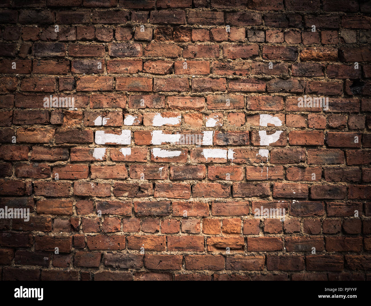 The Word Help Written As Graffiti On A Vintage Red Brick Wall - Stock Image