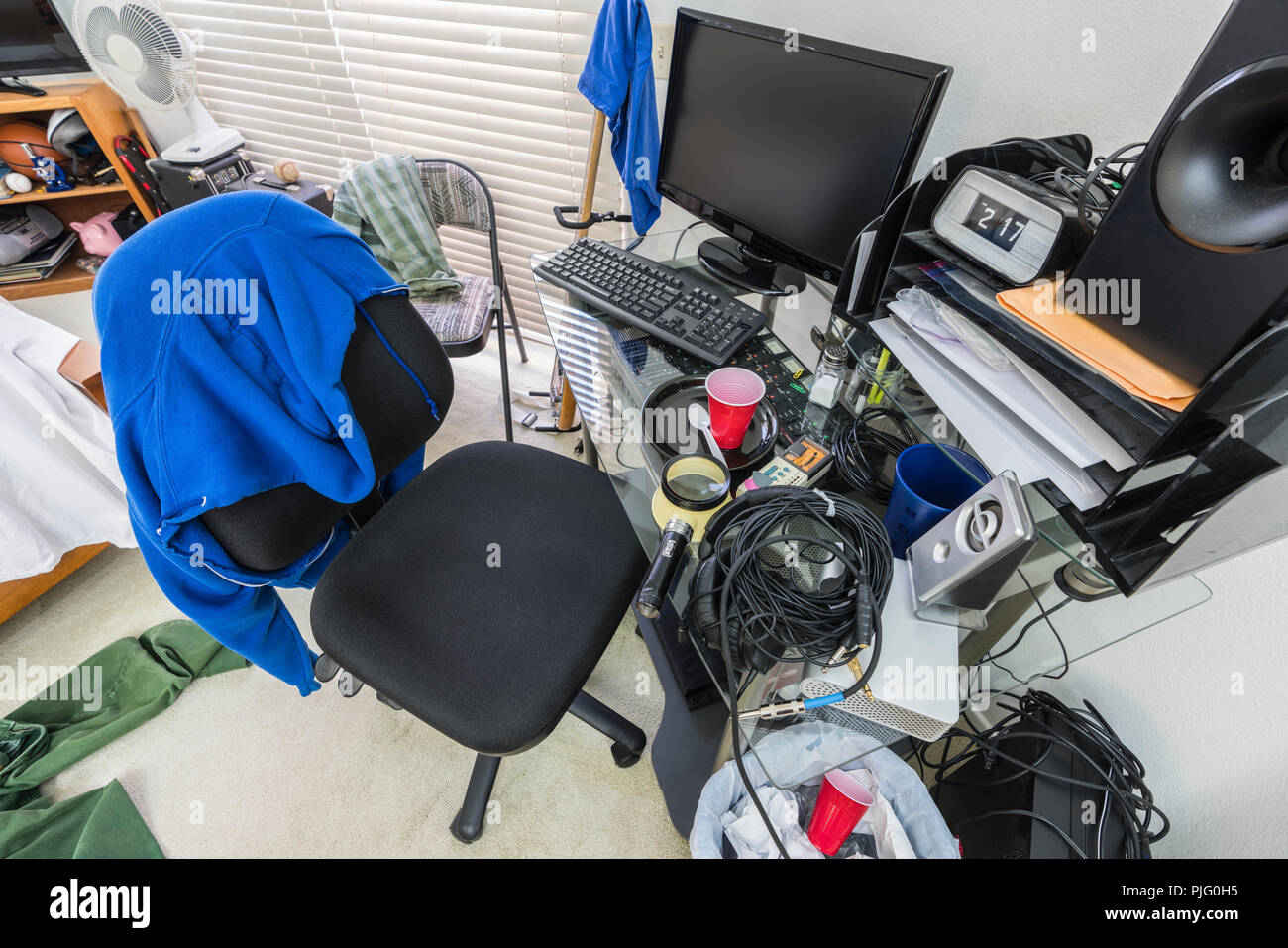 Messy, cluttered teenage boys bedroom desk and work area. - Stock Image