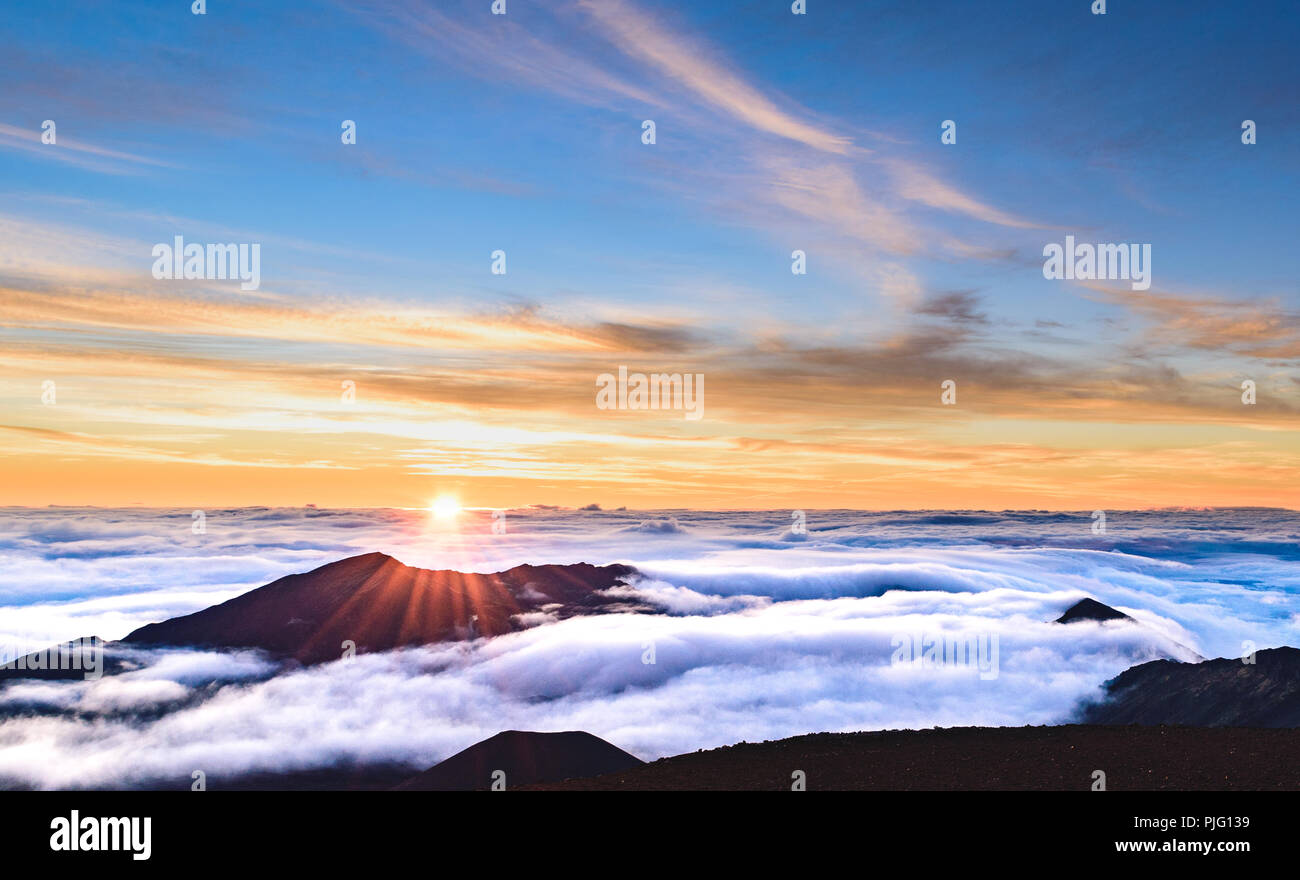 A blazing morning sun slowly rises over a shroud of clouds in the crater of Haleakala, a dormant volcano on the island of Maui, Hawaii - Stock Image