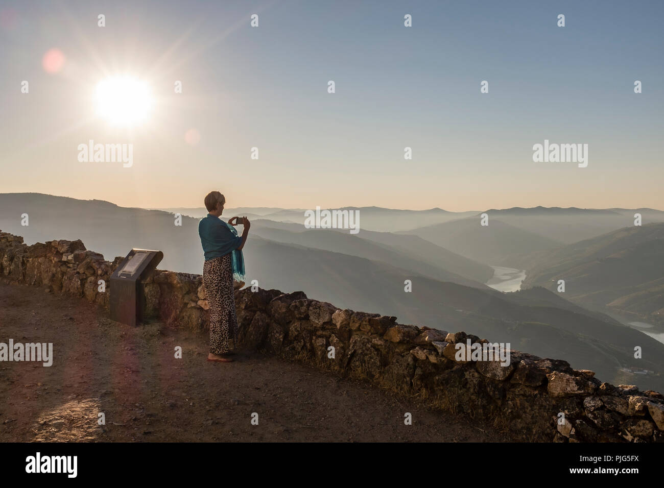 Woman taking a photo of a misty Douro Valley from viewpoint at São Leonardo de Galafura, Portugal - Stock Image