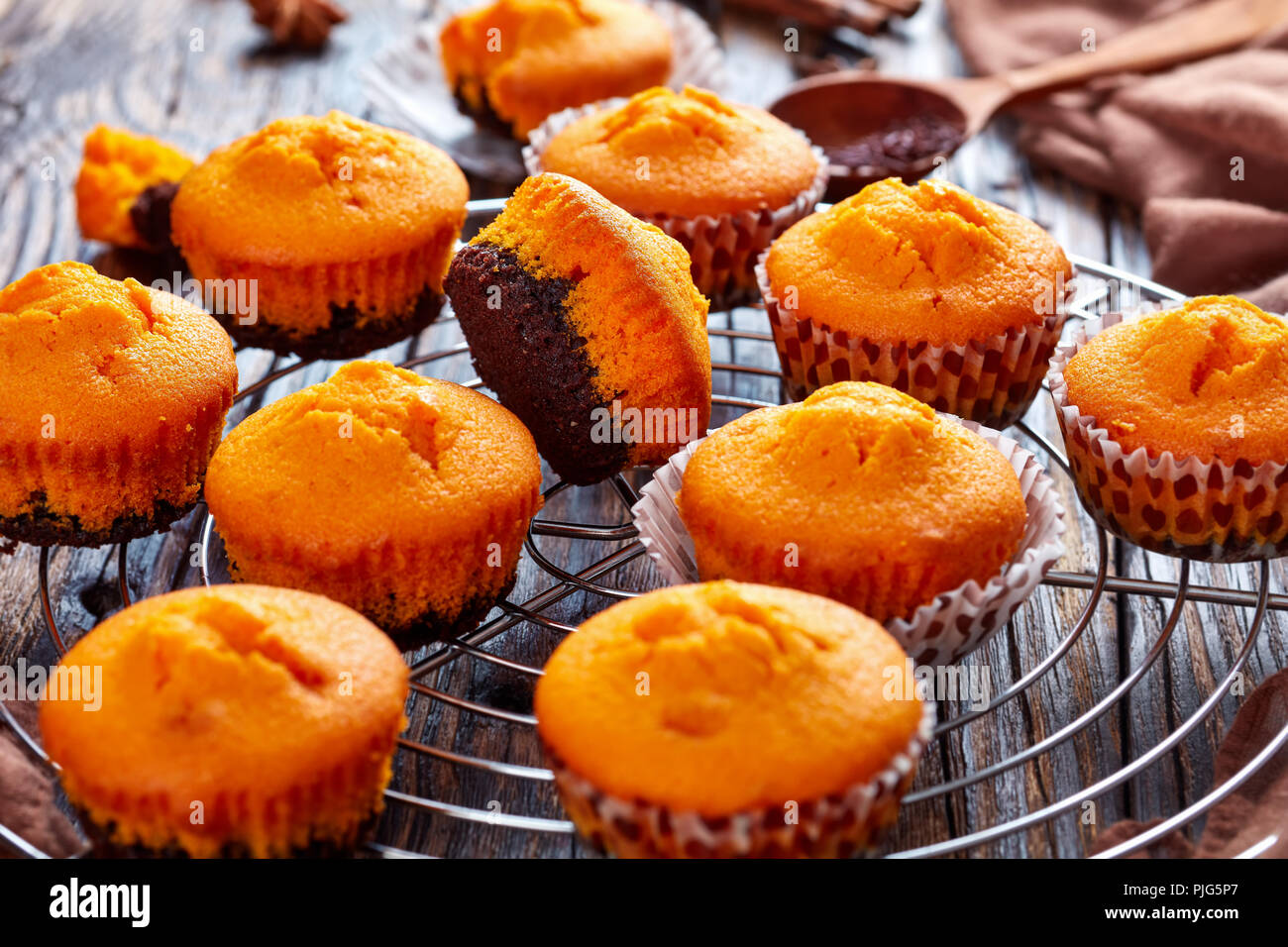 freshly baked delicious sweet pumpkin muffins  on a Round Stainless Steel Cake Cooling Rack on a rustic wooden table, delicious autumn dessert for hal - Stock Image