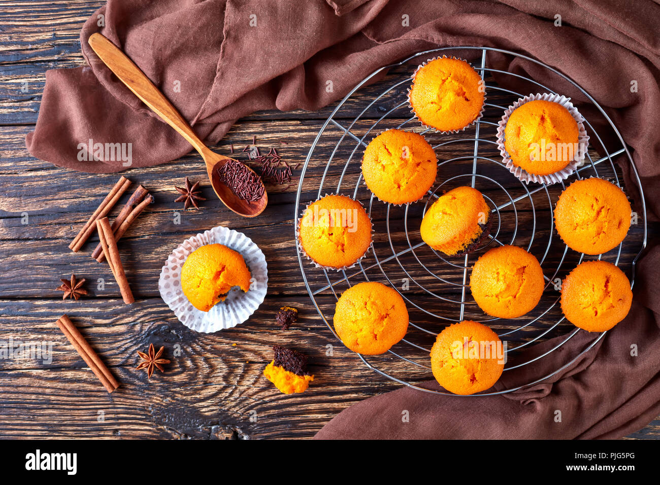 freshly baked homemade sweet pumpkin muffins  on a Round Stainless Steel Cake Cooling Rack on a rustic wooden table, delicious autumn dessert for hall - Stock Image
