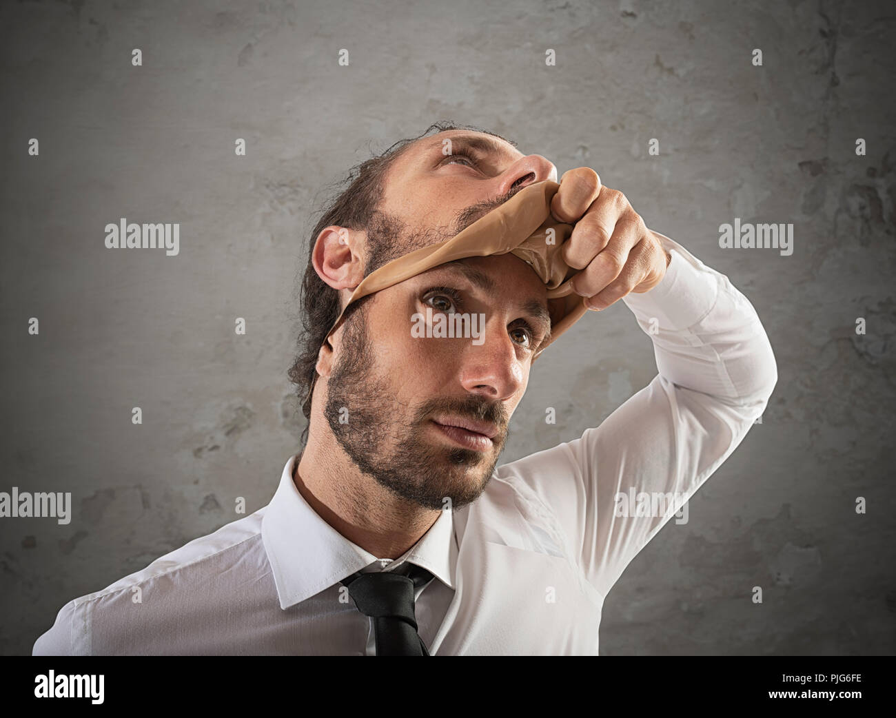 Businessman that removes the mask. Concept of falsity - Stock Image