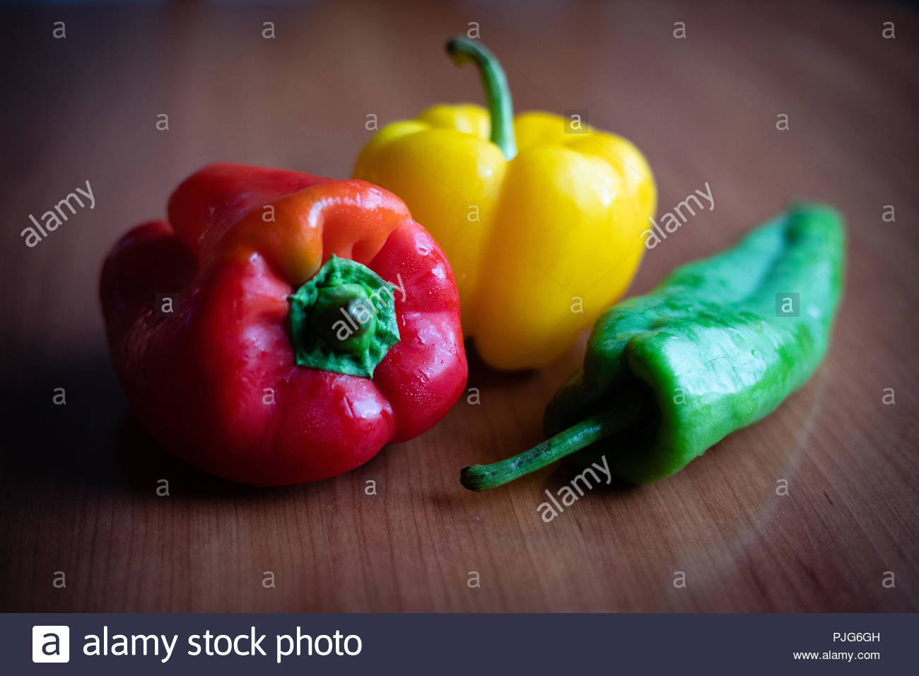 Red, yellow and green pepper on wooden table - Stock Image