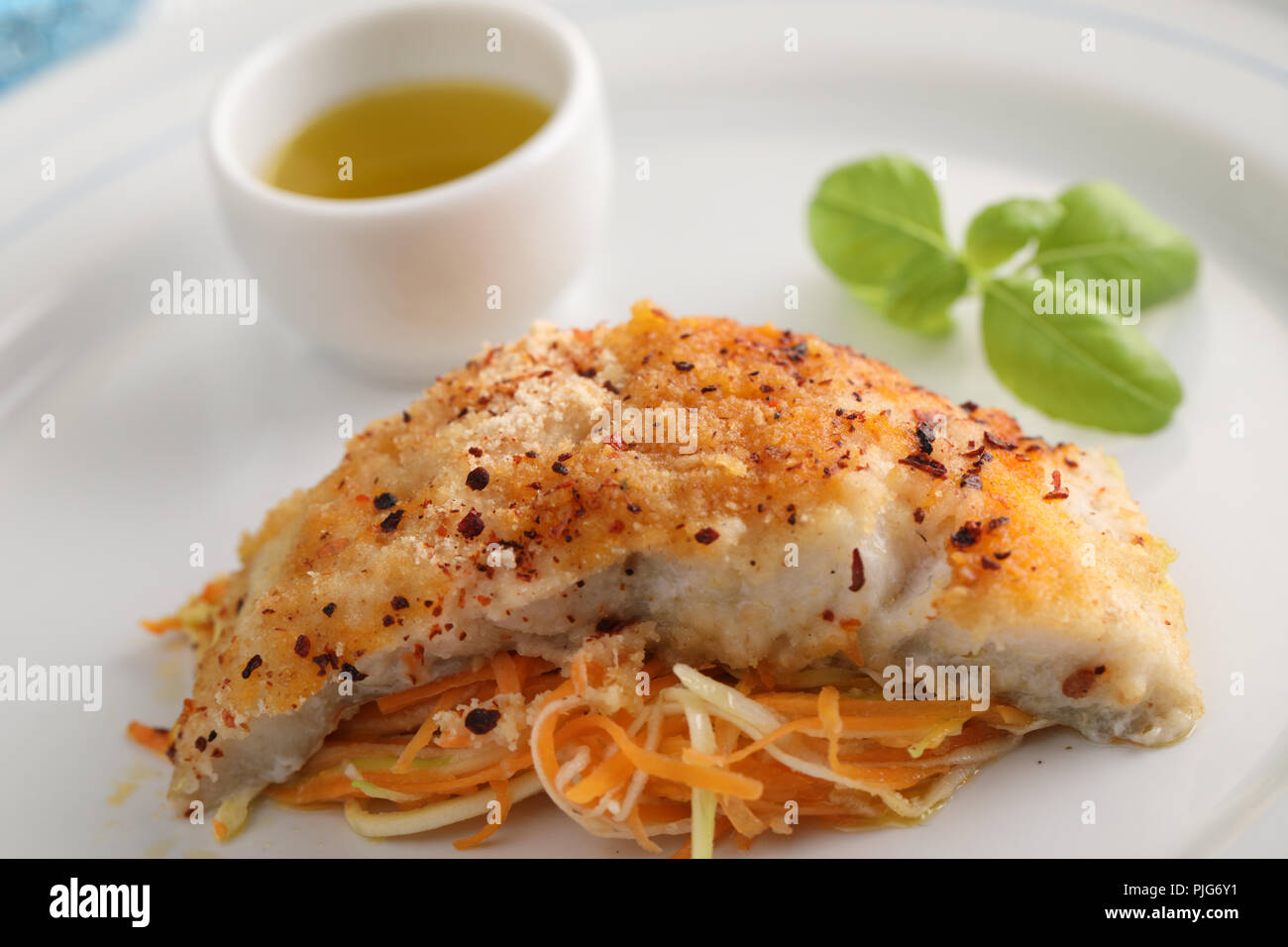 Baked breaded cod fish on vegetable bed topped with basil leaf - Stock Image