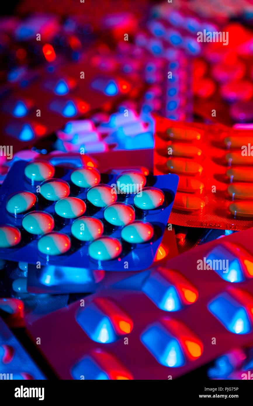Stack of pills in blister packs, colour gels, laboratory, dark