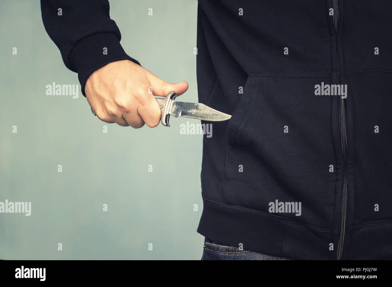 A maniac with a knife in his pocket. The murderer hides a small folding knife. Intimidation with a knife in the robbery. mafia. - Stock Image