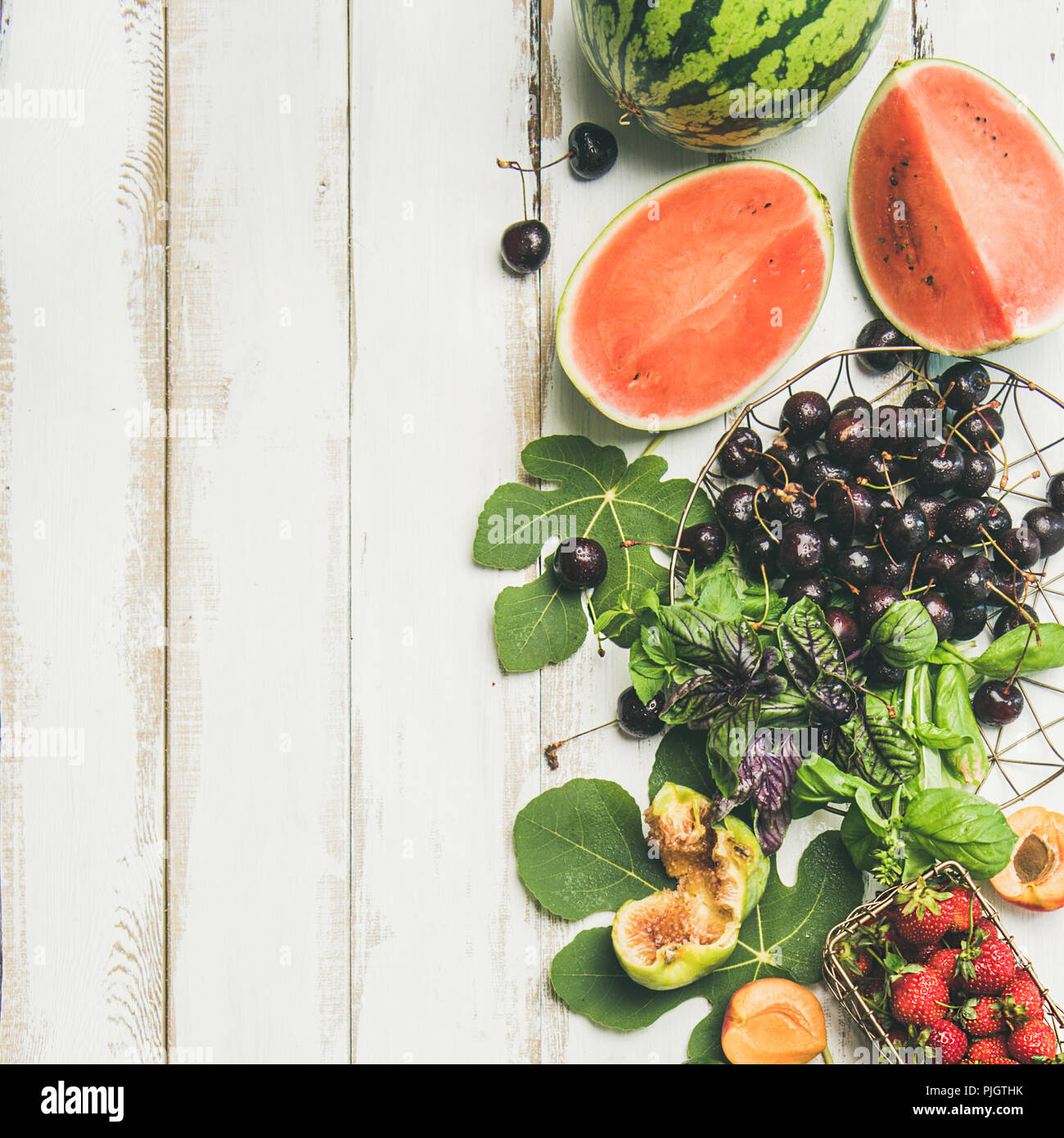 Summer food background. Flat-lay of seasonal fruit, vegetables and greens over white wooden background, top view, copy space, square crop. Vegetarian, - Stock Image
