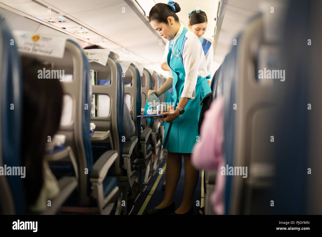 BANGKOK, THAILAND - Aug 27, 2018 - Bangkok Airways flight attendant serve food and drinks to passengers on board - Stock Image