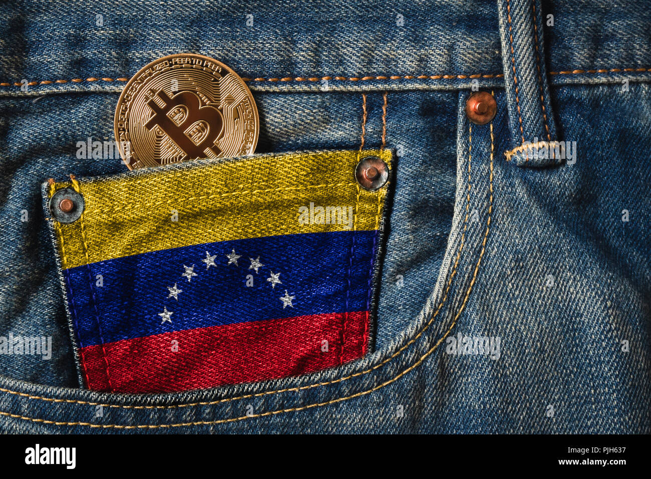 Golden BITCOIN (BTC) cryptocurrency in the pocket of jeans with the flag of Bolivarian Republic of Venezuela on Jeans Denim Texture. - Stock Image