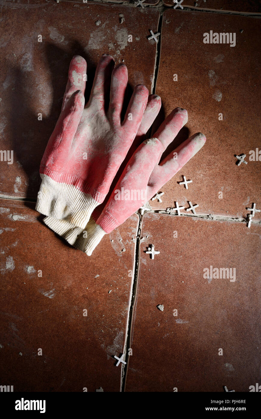 Messy protective gloves and tile spacers on a newly installed floor tiles - Stock Image