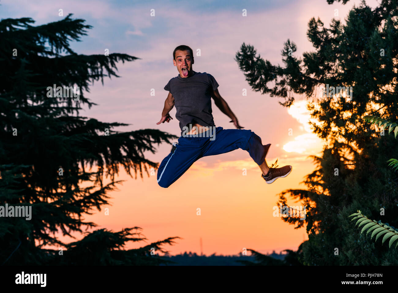 Free runner man exercise parkour outdoor while jumping - Stock Image