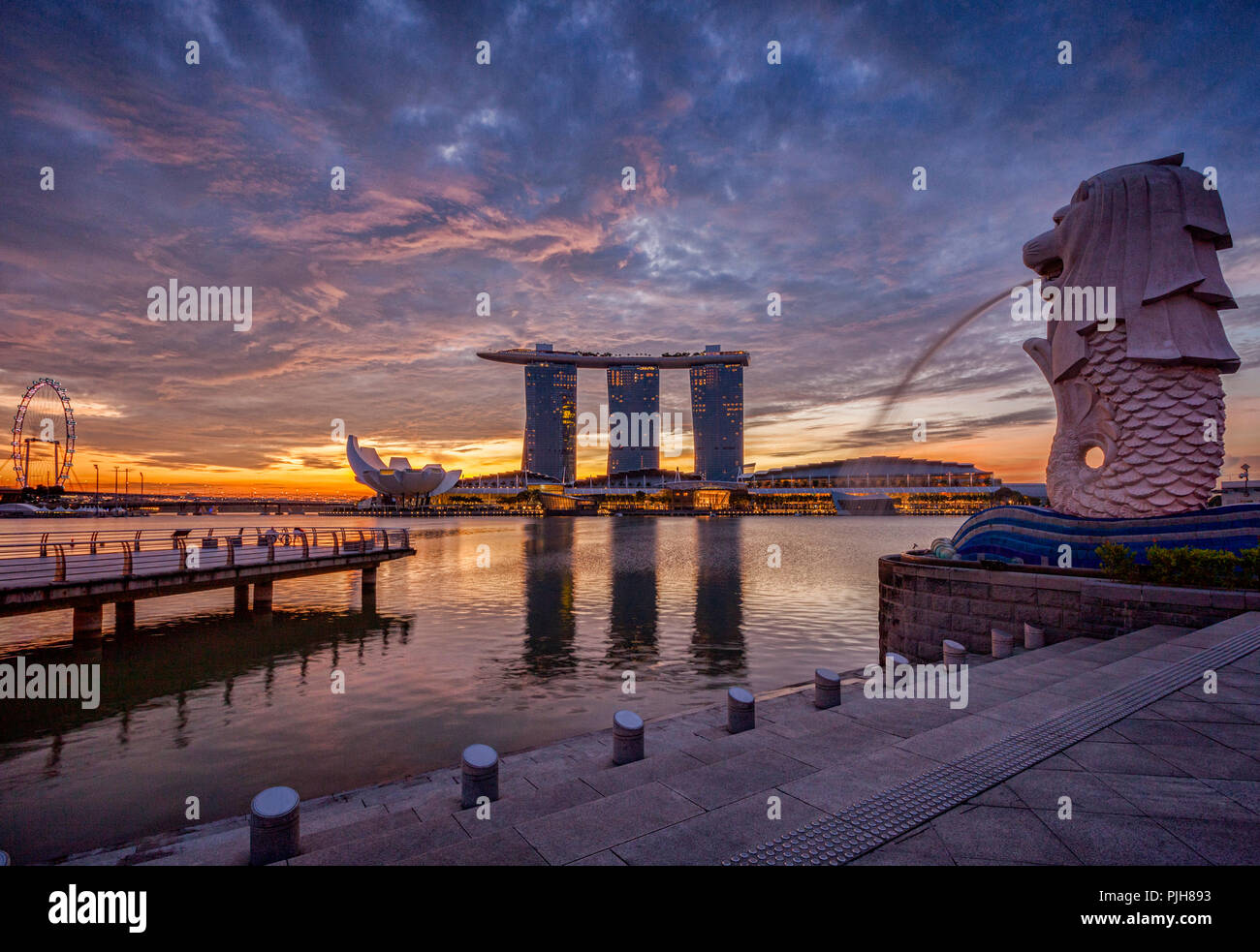 Singapore skyline at sunrise, with the Merlion, the Marina Bay Sands, the Art and Science Museum and the Singapore Flyer, all under a dramatic sky. - Stock Image