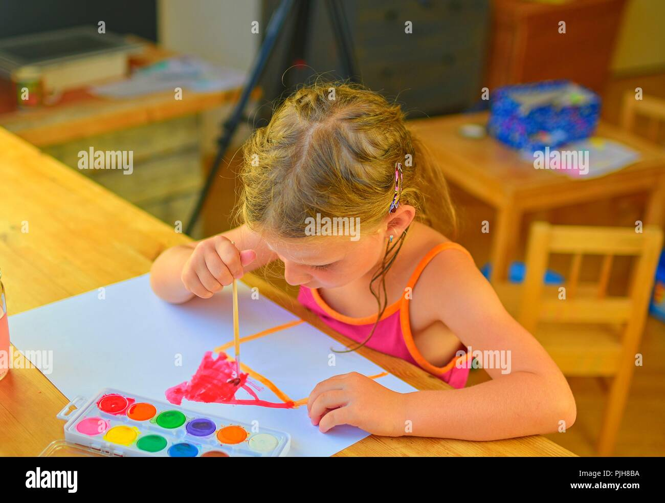 Little cute girl painting at her home. Selective focus and small depth of field - Stock Image
