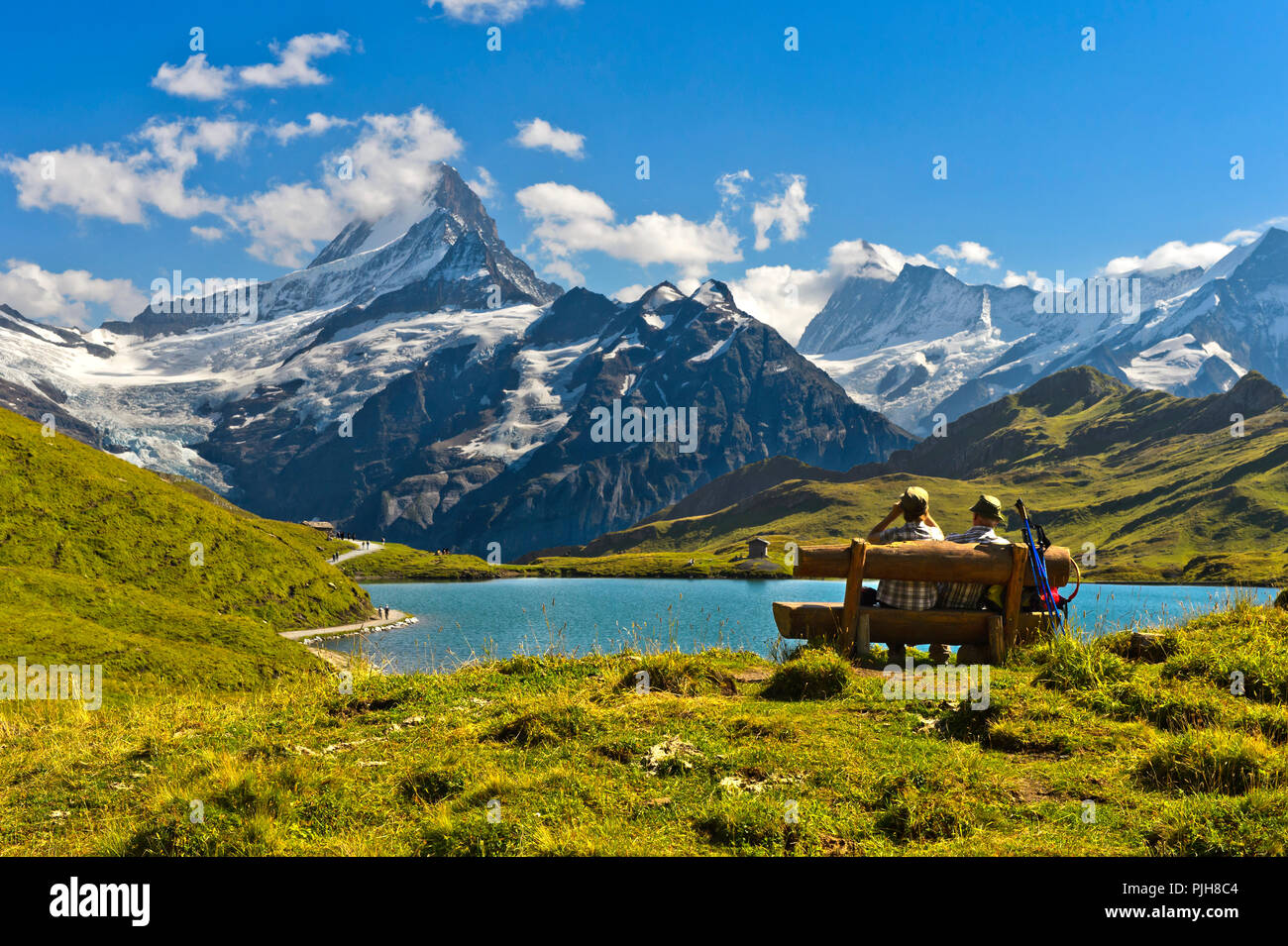 Hikers pausing on a wooden bench at lake Bachalpsee, behind the summits Schreckhorn and Finsteraarhorn, Grindelwald - Stock Image