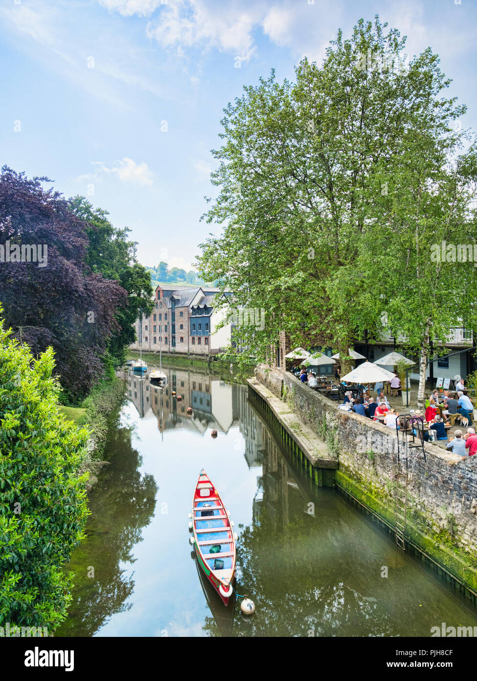25 May 2018: Totnes Devon UK - Trees and people at a restaurant beside the River Dart. Stock Photo