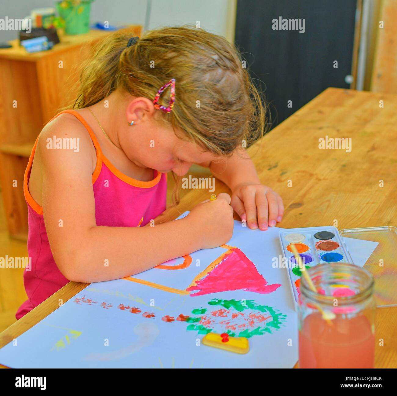 Cute little girl painting picture of house. Cute girl painting with watercolors. Mortage concept. Selective focus, small DOF - Stock Image