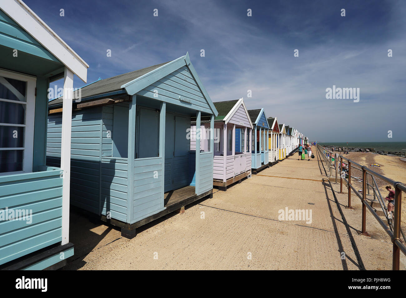 People relaxing in front of a line of beach huts during the heatwave of 2018 at Southwold, Suffolk, UK. - Stock Image