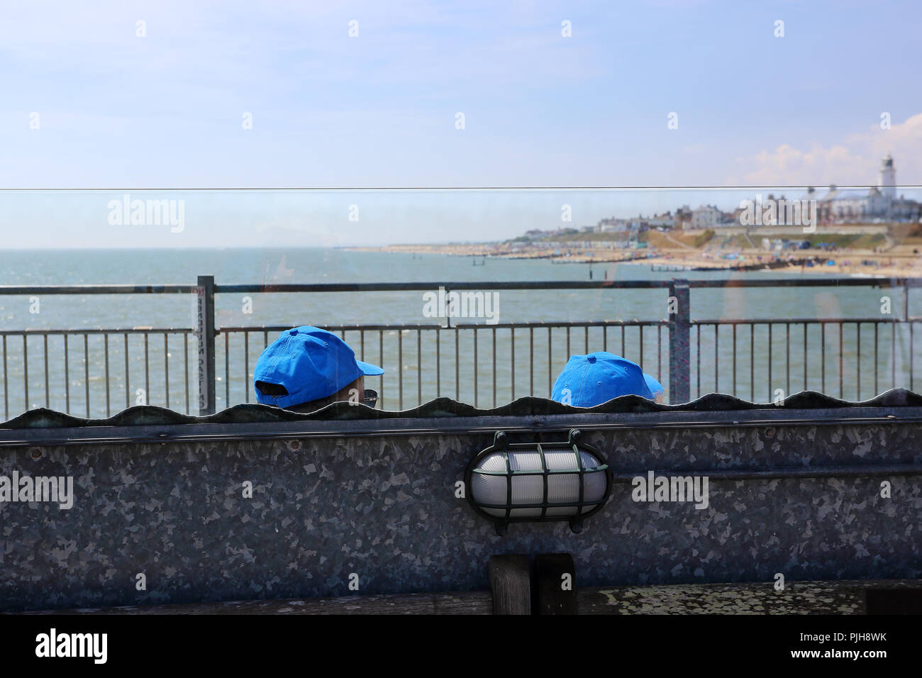 Two people, recogniseable only by their baseball caps, sit on a bench gazing out to sea at Southwold, Suffolk, UK. - Stock Image