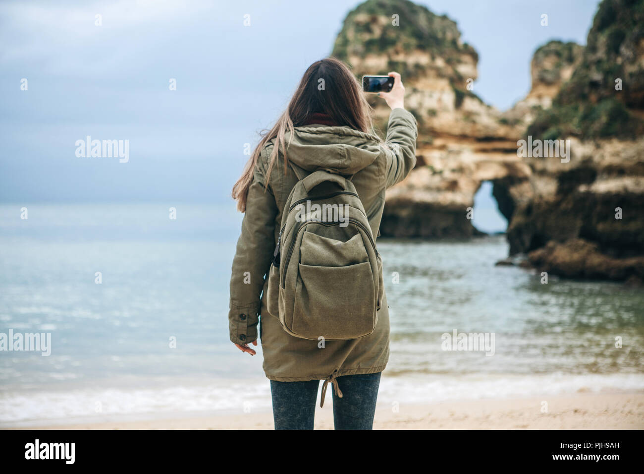Girl tourist with a backpack photographing a beautiful landscape standing on the Atlantic coast.Stock Photo