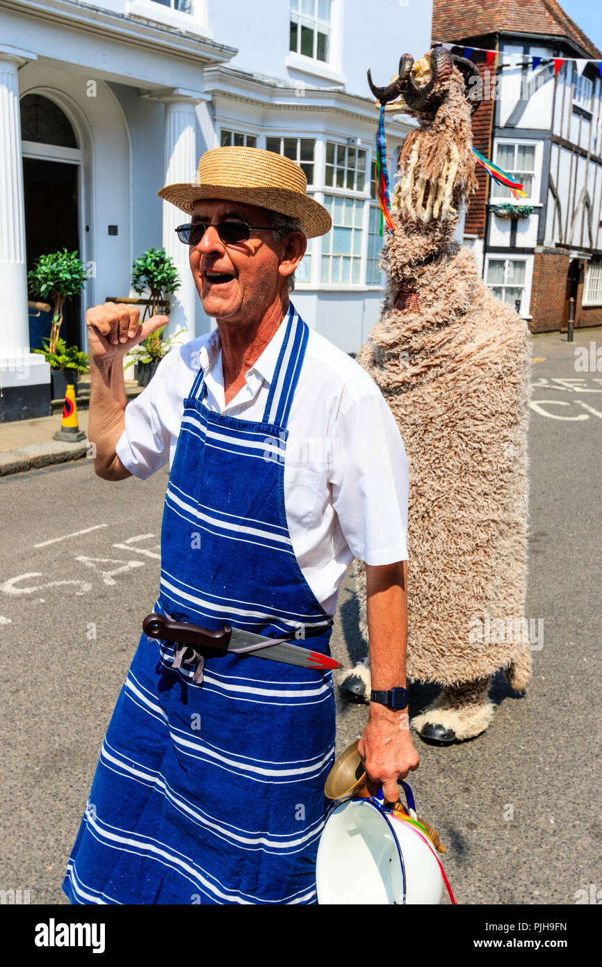The Thameside Mummers perform a mummer play in the medieval town of Sandwich. Senior man dressed as traditional butcher, behind, man dressed as ram. - Stock Image