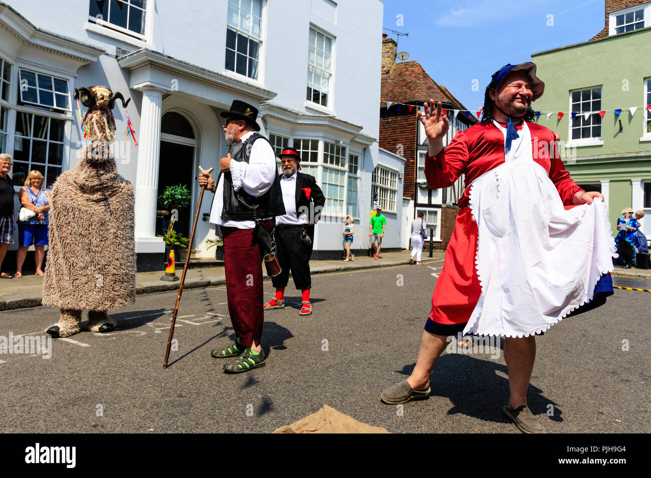 The Thameside Mummers perform a mummer play in the medieval town of Sandwich. Men dressed up as various characters including a ram and housewife. - Stock Image