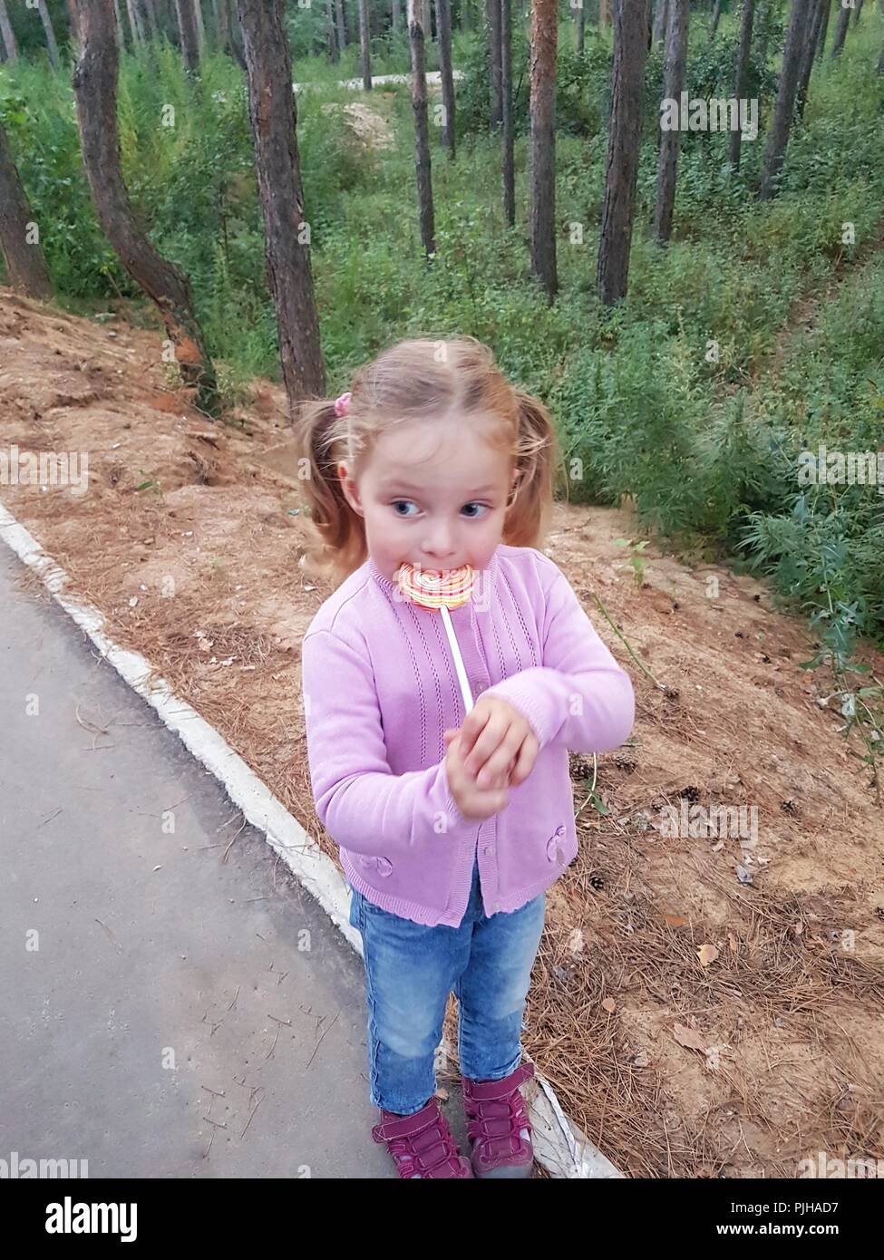 Funny child with candy lollipop, happy little girl eating big sugar lollipop, kid eat sweets. surprised child with candy. - Stock Image