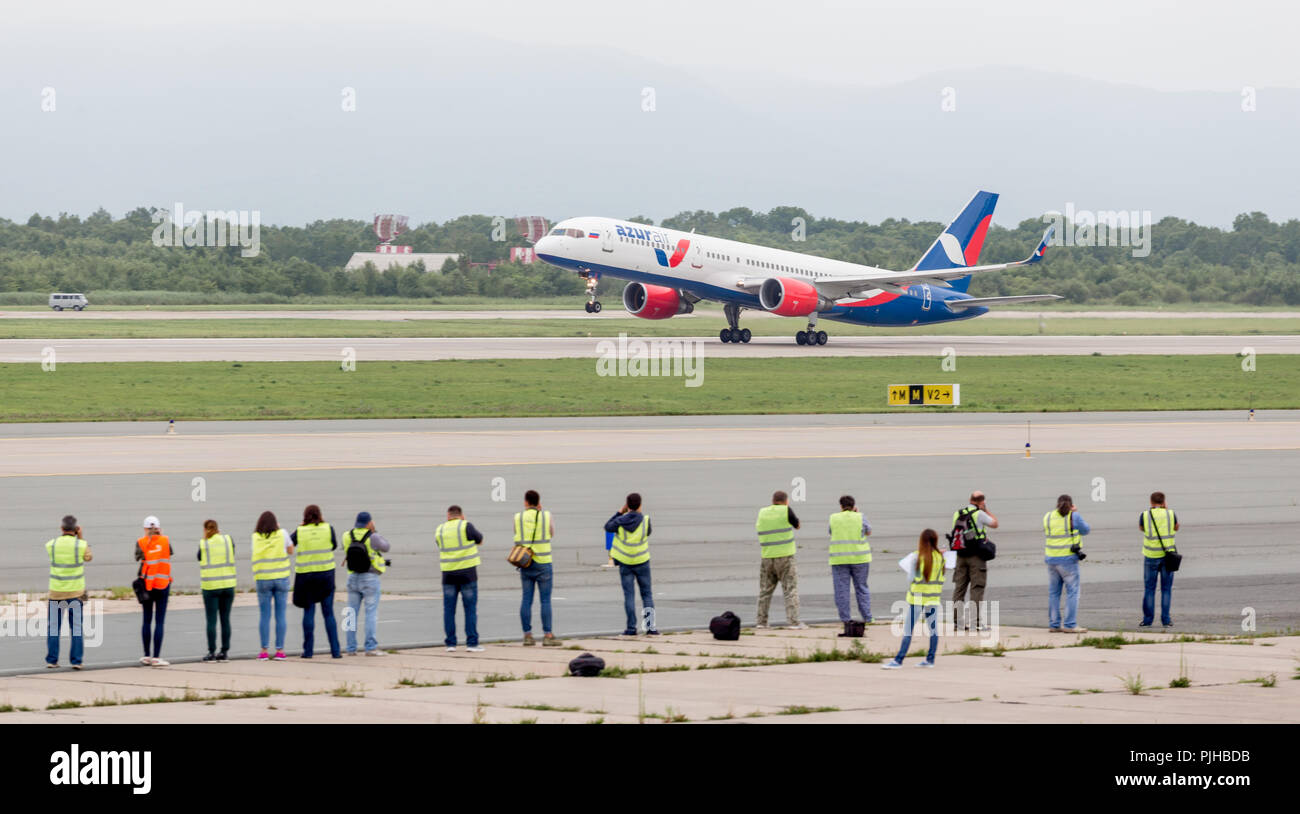 Russia, Vladivostok, 08/10/2018. Modern passenger airplane Boeing 757 of Azura Air takes off in cloudy day. Few photographers watch and make photo of  - Stock Image
