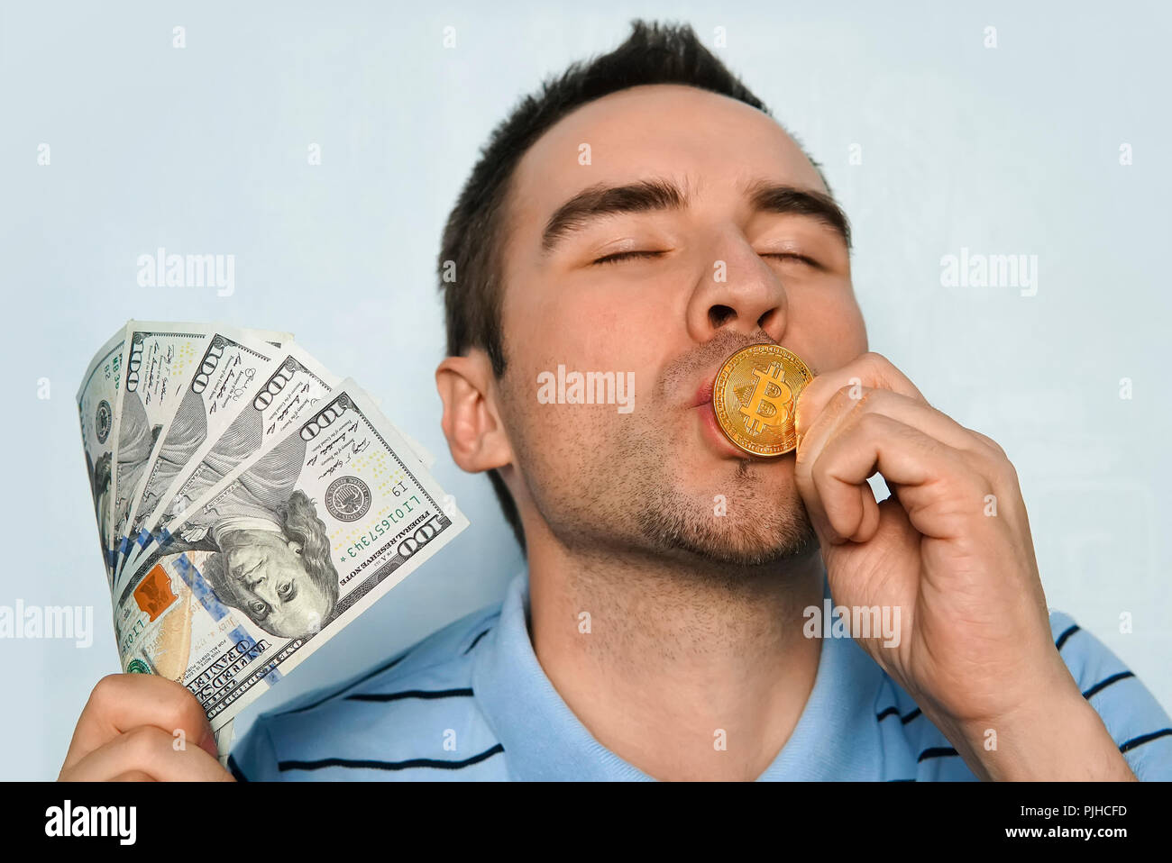 a man with a gold coin and dollars. Bitcoin curreny on united states hundred dollar bill with concept of earning money on bank spending. Miner earned  - Stock Image
