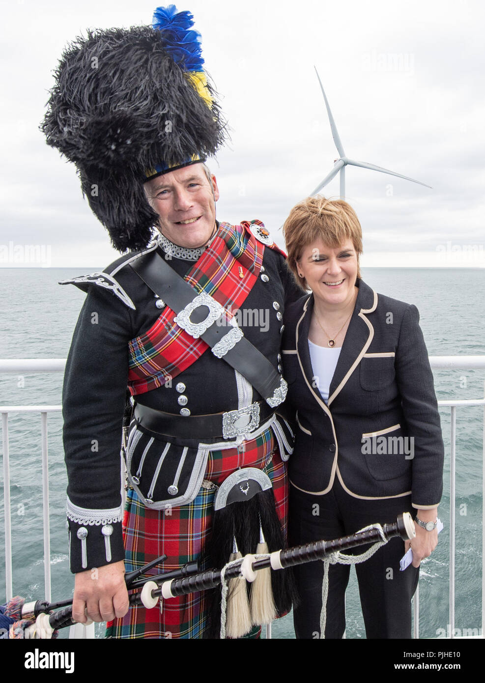 First Minister Nicola Sturgeon and with piper Norman Fiddes at the opening of Vattenfall's European Offshore Wind Deployment Centre (EOWDC) off the coast of Aberdeen. - Stock Image