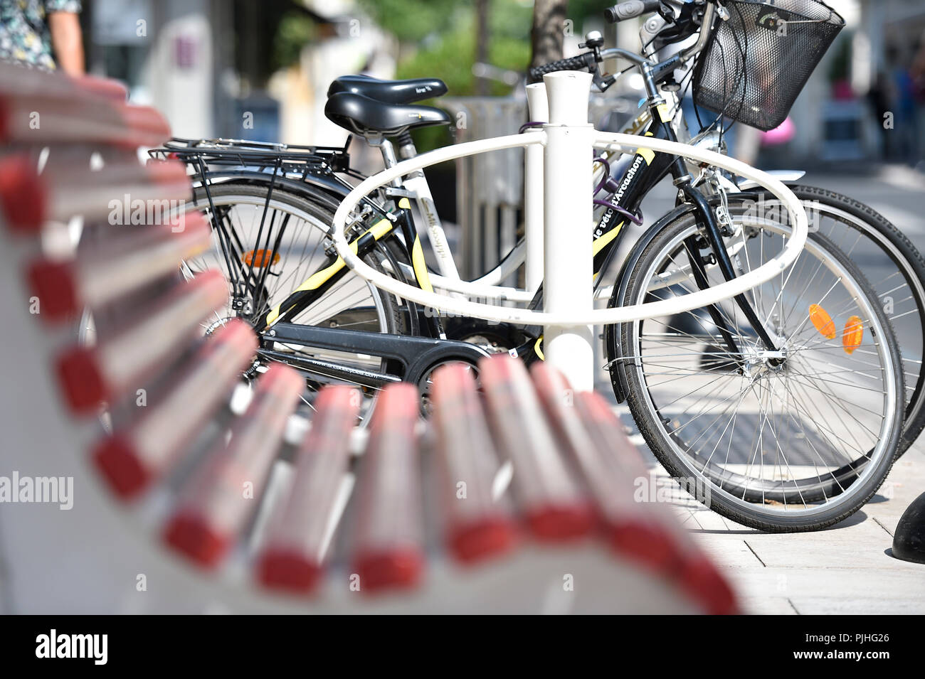 France , Arcachon, downtown, a red bench in the foreground and blur . Station bicycle attachment , in the background - Stock Image